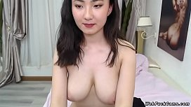 Petite brunette Asian amateur camgirl in underwear strips bra and panties and flashing her perfect big tits then wearing in bed in live webcam show