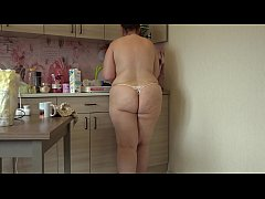 Cheerful chubby with a fat butt prepares pancakes and removes clothes.