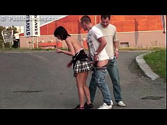 Little young chick is fucked in public in the middle of a street by two guys